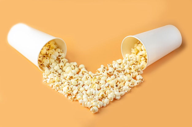Concept de films d'amour. pop-corn dans une boîte en papier dispersée sur fond orange en forme de coeur vue de dessus, copiez l'espace pour le texte. concept de collation de cinéma. mocap boîte à pop-corn