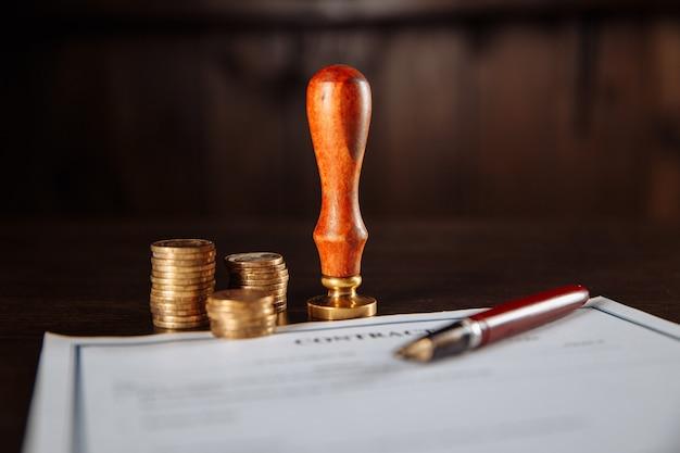 Le concept de la finance et des affaires. contrat, tampon, argent et stylo sur une table.