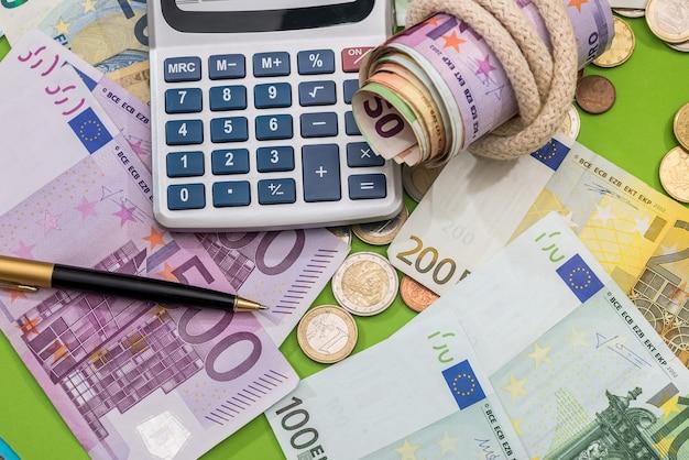 Concept de finances billets et pièces en euros avec calculatrice et stylo
