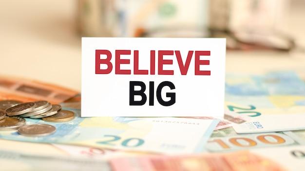 Concept de finances et d'économie. sur la table se trouvent des billets, des pièces de monnaie et un panneau sur lequel il est écrit - croyez en grand.