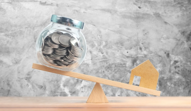 Concept financier hypothécaire immobilier maison d'investissement, maison modèle et pièces d'argent en équilibre sur balançoire