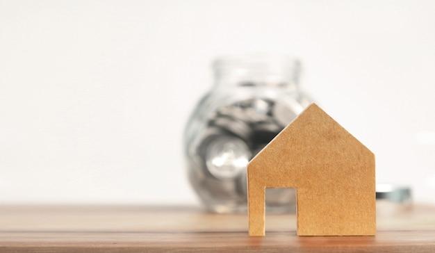 Concept financier d'investissement immobilier et d'hypothèque, main mettant la pièce d'argent