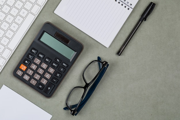 Concept financier avec ordinateur portable, papier, stylo, calculatrice, clavier, lunettes sur fond plat gris.