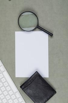Concept financier avec portefeuille, papier, loupe, clavier sur fond plat gris.