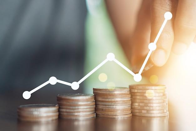 Concept financier réussi avec tendance haussière graphique de l'icône et pile de pièces d'or sur table.