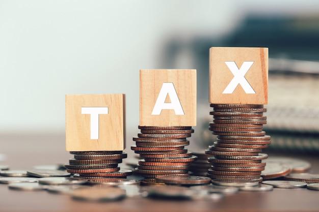 Concept fiscal avec des cubes en bois avec le mot taxe sur les pièces empilées