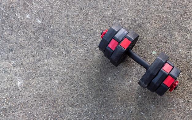 Concept de fitness ou de musculation. haltères gros plan sur fond de ciment.