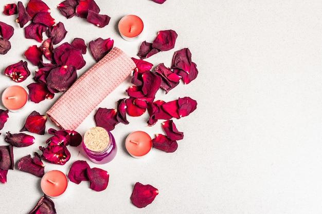 Concept floral et spa avec pétales de roses séchées, bougies parfumées et serviette douce
