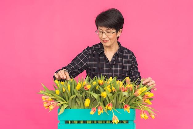 Concept de floristique, de vacances et de personnes - femme d'âge moyen tenant une boîte de tulipes sur un rose
