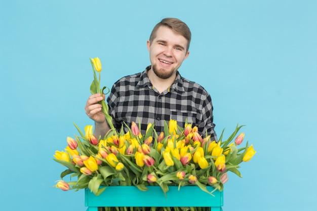 Concept floristique, vacances et personnes - jardinier homme fixant un bouquet de tulipes sur fond bleu