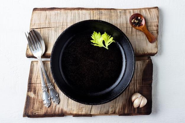Concept de fond de cuisine. assiette en fonte noire rustique vide, épices et couverts.