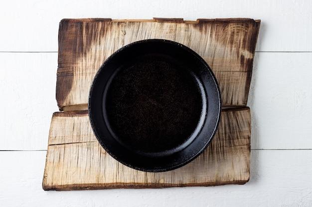 Concept de fond de cuisine. plaque en fonte noire rustique vide sur fond de bois.