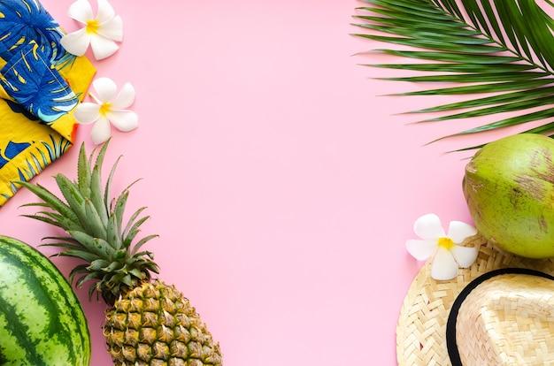 Concept de fond d'été avec chapeau de plage, noix de coco, ananas, pastèque, fleurs de frangipanier et chemise colorée sur fond rose