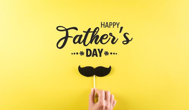 Concept de fond de fête des pères heureux avec la main tenant la moustache noire avec le texte