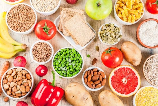 Concept de fond de régime alimentaire, produits de glucides sains - fruits, légumes, céréales, noix, haricots, fond de béton clair ci-dessus