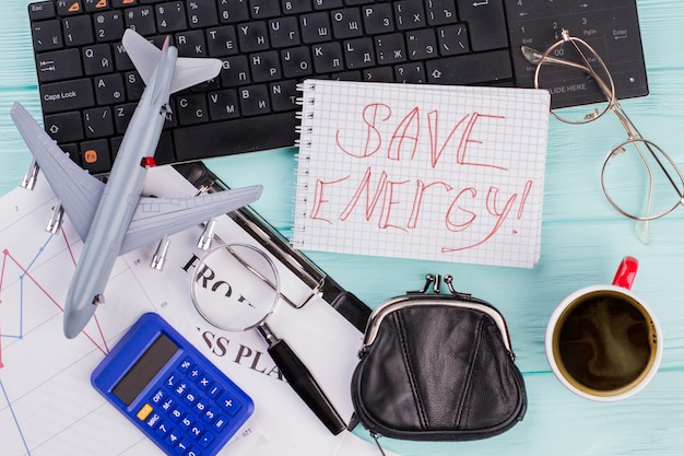 Concept de fond de vacances de voyage avec ordinateur portable, tasse de café, avion sur fond en bois turquoise. la calculatrice est le symbole du coût du repos.