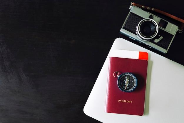 Concept de fond de voyage. passeport, boussole, appareil photo et ordinateur portable sur tableau noir