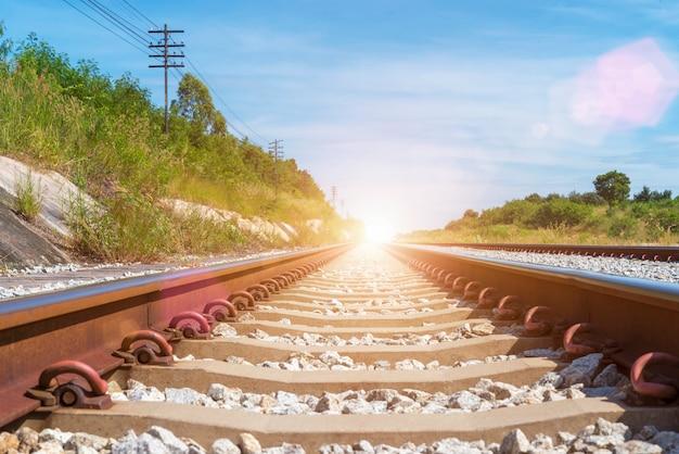 Concept de fond de voyage et de transport. voie ferrée vide avec un ciel bleu à sunris