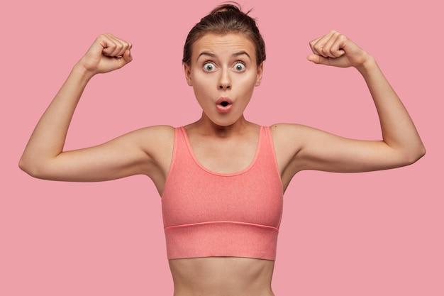 Concept de force et de féminisme. surpris jeune sportive européenne en haut décontracté rose montre les muscles de la main
