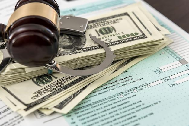 Le concept de formulaire fiscal nous argent avec le marteau de menottes se trouvant sur l'impôt fédéral