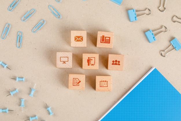 Concept de fournitures de bureau avec des icônes sur des cubes en bois, ensemble de papeterie à plat.