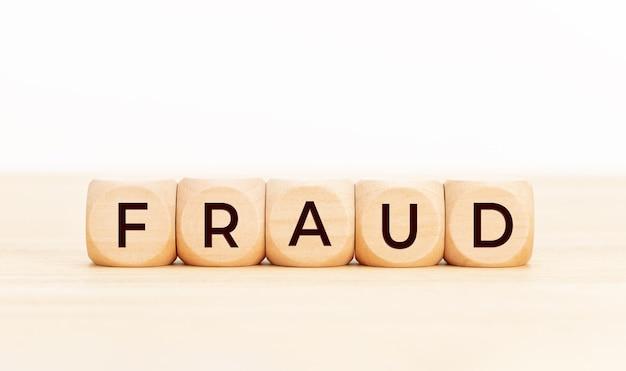 Concept de fraude. blocs en bois avec texte sur table.