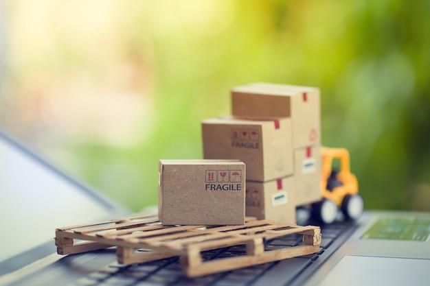 Concept de fret logistique et cargo chariot élévateur à fourche un camion déplace une boîte en papier sur le clavier de l'ordinateur portable