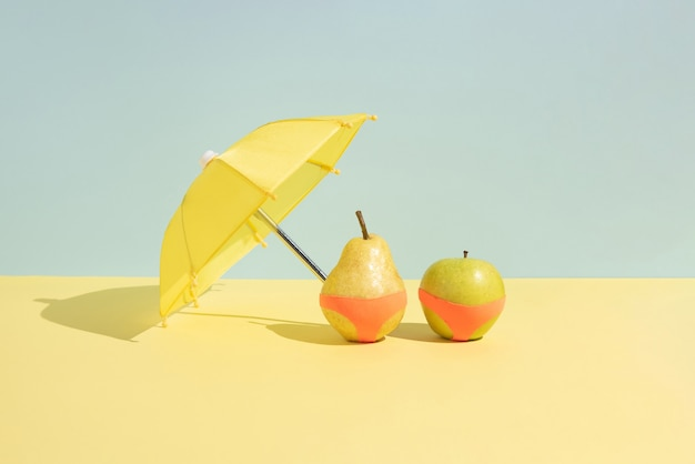 Concept de fruits d'été. pomme mouillée et poire en monokini à côté d'un parapluie isolé sur fond bleu et jaune. abstrait. disposition rectangulaire avec espace de copie