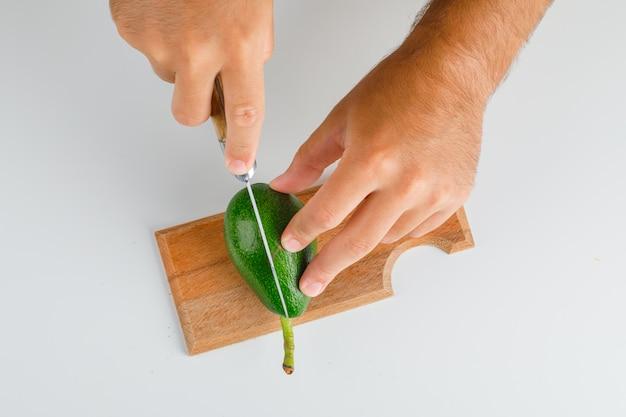Concept de fruits à plat. mains coupe avocat sur planche de bois.