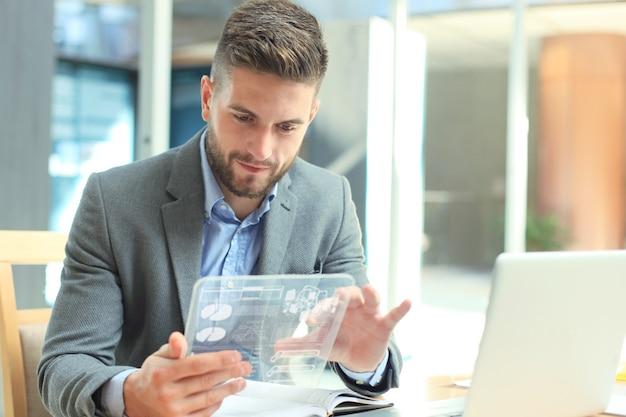 Concept futur. homme d'affaires analysant les statistiques financières affichées sur l'écran de la tablette transparente futuriste.