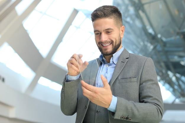 Concept futur. l'homme d'affaires détient un téléphone intelligent transparent futuriste.