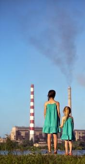 Concept futur de soins. les sœurs regardent les cheminées qui polluent l'air