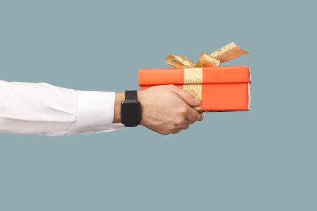 Concept de gens d'affaires, richement et succès. main humaine en chemise blanche avec des montres intelligentes noires tenant une boîte-cadeau rouge avec ruban d'or. vue de côté de profil. intérieur, tourné en studio sur fond bleu clair