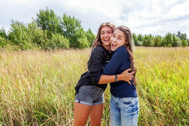 Concept de gens heureux vacances vacances d'été. groupe de deux amies danser étreindre et s'amuser ensemble dans la nature en plein air. bons moments meilleur ami.