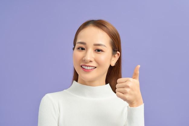 Concept de geste et de personnes - souriante jeune femme asiatique montrant les pouces vers le haut sur le mur violet