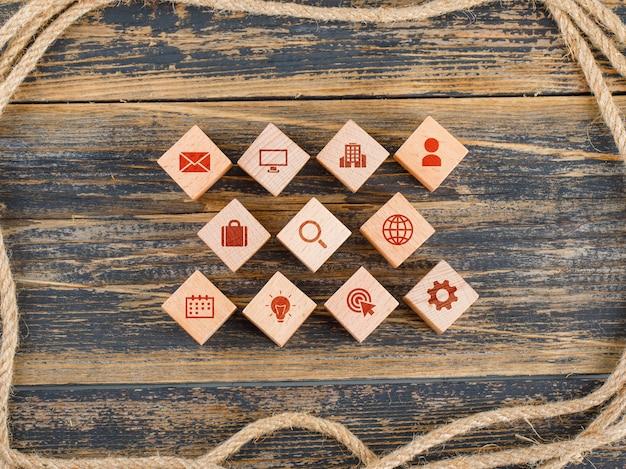 Concept de gestion avec des blocs en bois avec des icônes sur la table en bois à plat.