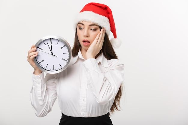 Concept de gestion du temps - jeune femme d'affaires avec bonnet de noel tenant une horloge isolée sur un mur blanc.