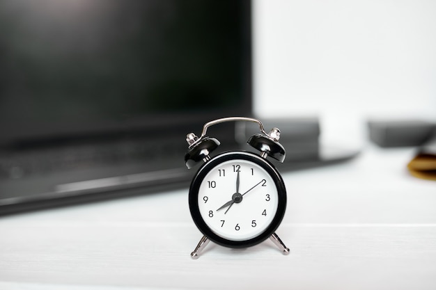 Concept de gestion du temps, lieu de travail de bureau, ordinateur portable, ordinateur, ordinateur portable et réveil noir sur un bureau en bois blanc, espace de copie.