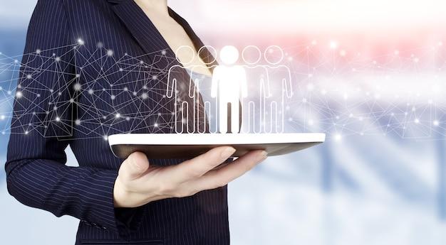 Concept de gestion des ressources humaines et de l'équipe. tenir à la main une tablette blanche avec hologramme numérique humain, signe de leader sur fond flou clair. concept de communication d'entreprise. commercialisation. travail en équipe.