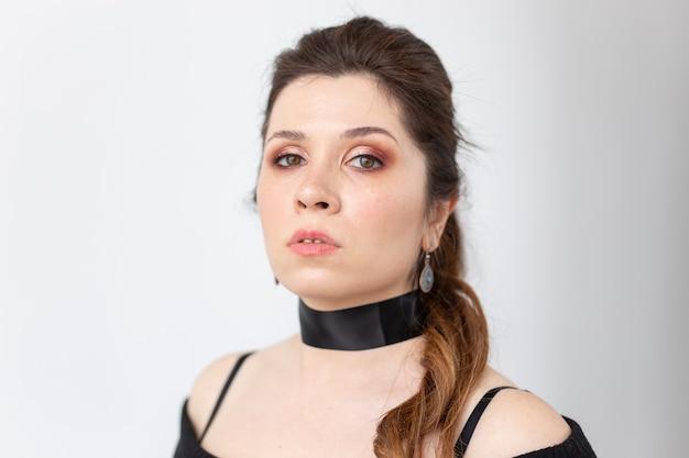 Concept gothique, maquillage, mode et people - jeune femme belle élégante à la peau blanche et rouge