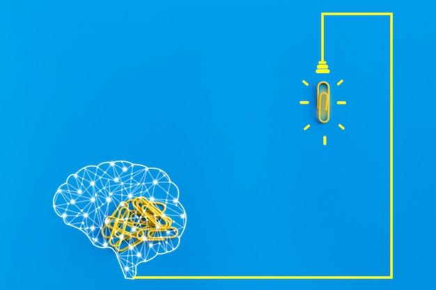 Concept de grandes idées avec cerveau humain, trombone, pensée, créativité, ampoule sur fond bleu, nouveau concept d'idées