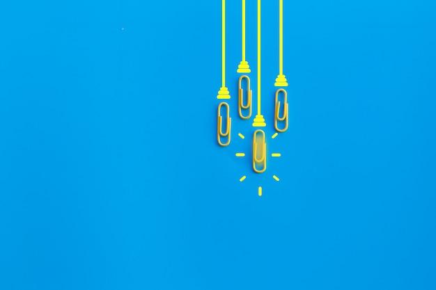 Concept de grandes idées avec trombone, réflexion, créativité, ampoule sur fond bleu, nouveau concept d'idées.