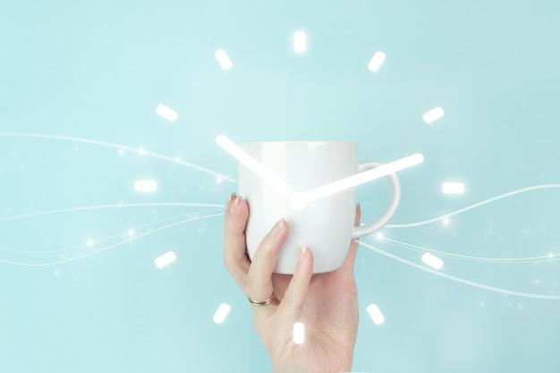Concept graphique d'intervalle de durée de gestion du temps. vue recadrée de la main féminine avec une tasse à café blanche et une icône de signe d'horloge sur fond bleu.