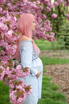 Concept de grossesse, d'amour, de personnes et d'attentes. femme enceinte, dans, robe bleue, à, sakura, fleurir, arbre