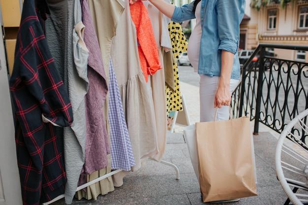 Concept de grossesse, de maternité, de personnes et d'attentes - gros plan d'une femme enceinte avec des sacs à provisions dans la rue de la ville.