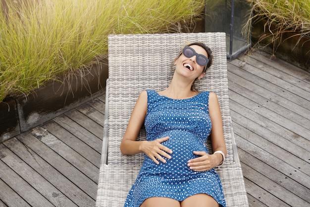 Concept de grossesse et de maternité. vue de dessus de la belle femme enceinte heureuse dans les tons allongé sur une chaise longue et toucher son ventre.
