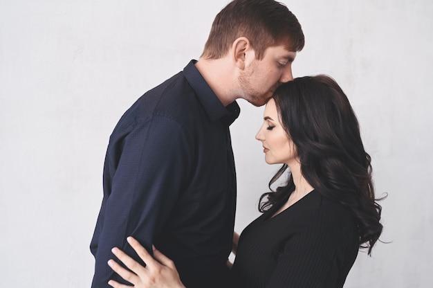 Concept de grossesse et de personnes. homme heureux étreignant sa belle femme enceinte à la maison. futurs parents attendant bébé à naître.