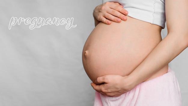 Concept de grossesse. ventre d'une fille enceinte avec les mains