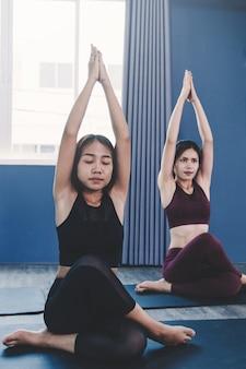 Concept de groupe de yoga; les jeunes pratiquant le yoga en classe; sentir le calme et se détendre en cours de yoga