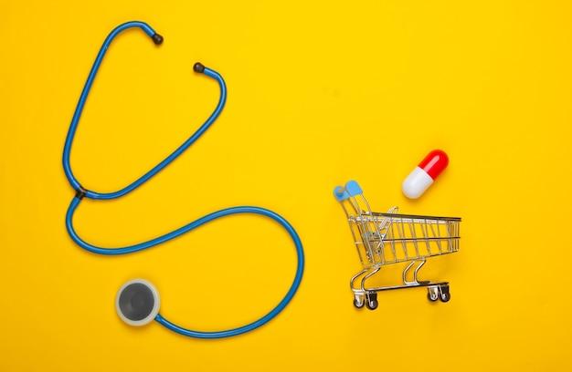 Le concept de guérison. composition à plat. stéthoscope, caddie avec capsule sur fond jaune. vue de dessus
